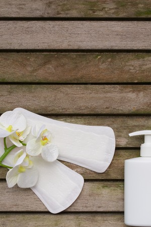 premenstrual: Everyday female pantyliners with artificial orchids heads and a plastic bottle of in time gel on a wooden surface covered by moss. Background.
