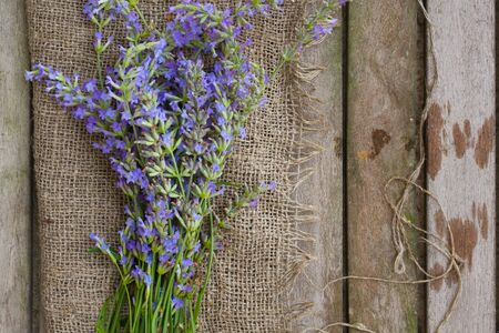Lavender twigs on a sackcloth placed on an old wooden surface. Overhead perspective.
