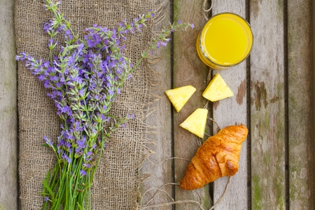 pineapple juice: Summer breakfast in the village: French croissant with fresh pineapple juice in the glass on a wooden surface. Lavender twigs on a sackcloth. Overhead perspective.