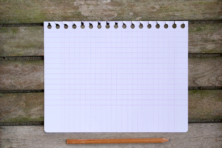 millimetre: A  checkered sheet of paper from agenda on an old wooden surface. Background Stock Photo