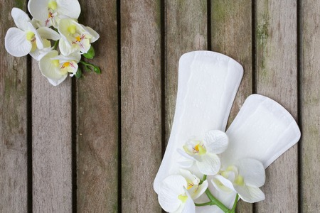 premenstrual: Everyday female pantyliners with artificial orchids heads on a wooden surface covered by moss. Background.
