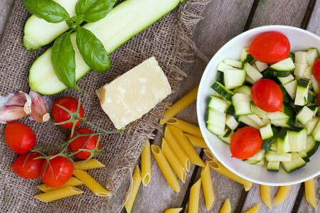 rebate: Food ingredients for preparing pasta: zucchini, penne rebate,cherry tomatoes,parmesan cheese, fresh basil leaves, garlic on an old wooden surface. Overhead perspective