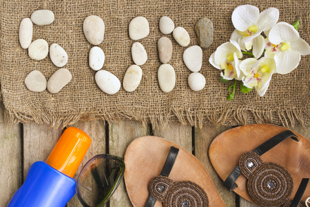 Summer protective items for a woman: sun protection lotion spf,sun eyeglasses, leather summer shoes on a wooden surface covered by moss. Stock Photo
