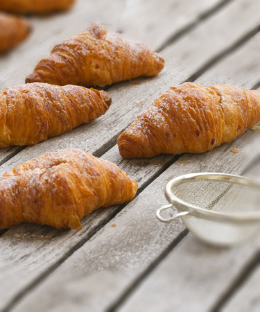 flaky: French crescent-shaped roll made of sweet flaky yeast dough- croissant covered by sugar powder placed on a gray wooden surface. A tea strainer in the background. Stock Photo