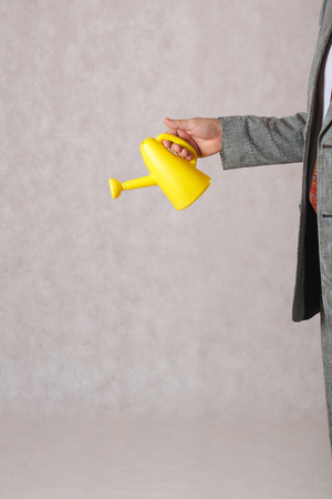 career development: A yellow watering can kept by a man dressed in a classical costume.