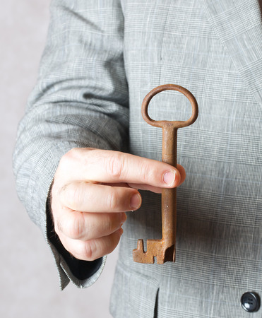vintage key: A vintage key in the hand of a man in a classical costume.Closeup