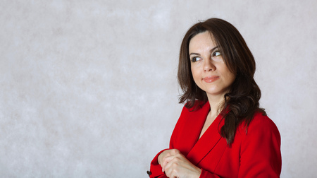 between 30 and 40 years: A young woman between 30 and 40 years old dressed in a classical red jacket reflects on something Stock Photo