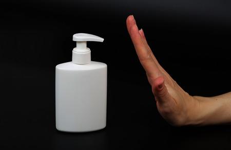 desinfectante: Dispensador con desinfectante y una m�scara en una background.Closeup negro