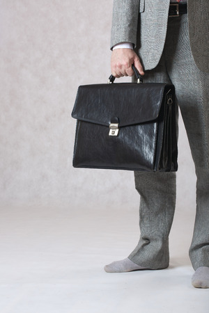A man in a classical costume but without shoes keeps his black office leather bag. Closeup. Free space for a text. Stock Photo