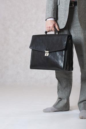 Człowiek w klasycznym stroju, ale bez butów zachowuje swoją czarną skórzaną torbę biurową. Closeup. Wolne miejsce na tekst.