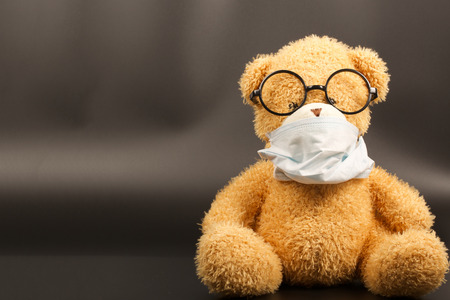 flue season: Teddy bear in a protective mask and eye glasses on a black background
