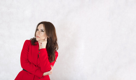 between 30 and 40 years: A young woman between 30 and 40 years old dressed in a classical red jacket is reflecting on something