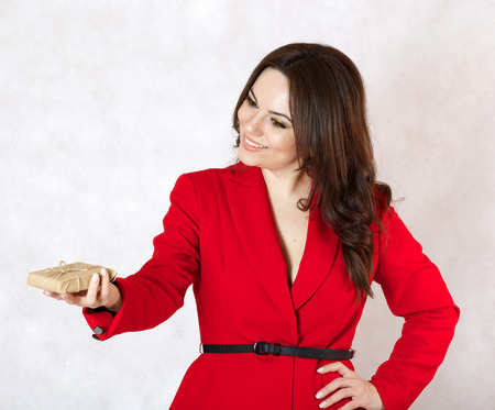 30 to 40 years: A young woman between 30 and 40 years old dressed in a classical red jacket gives a small parcel to someone,