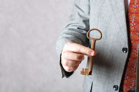 50 to 60 years: A vintage key in the hand of a man in a classical costume.Closeup