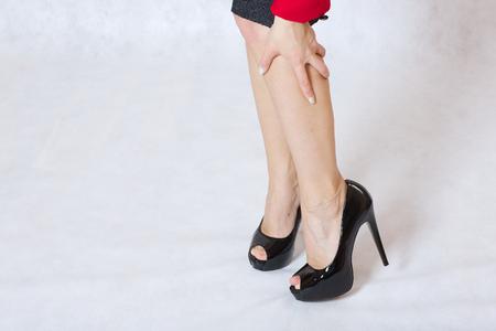 selfcare: Una mujer joven tiene una sensación de pesadez en sus hermosas piernas delgadas.