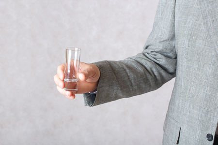 50 to 60 years: Vodka glass in the hand of a man. Closeup
