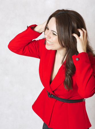 40 years old: A young woman between 30 and 40 years old dressed in a classical red jacket itches her head skin Stock Photo