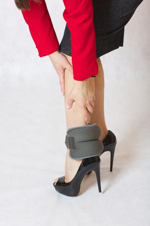 autocuidado: Una mujer joven en tacones altos tiene relleno de arena de tobillo en sus piernas.