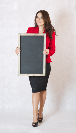 30 years old woman: A young woman between 30 and 40 years old dressed in a formal way keeps a black chalk board. Free space for a text Stock Photo