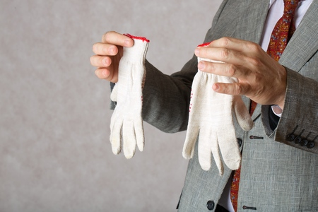 age 60: Gardening gloves kept by a man in a classical costume.Closeup