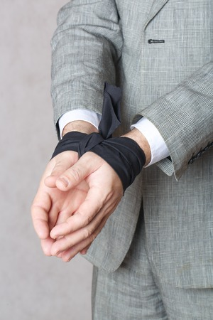 black fabric: Business mans hands tied with black fabric. Closeup