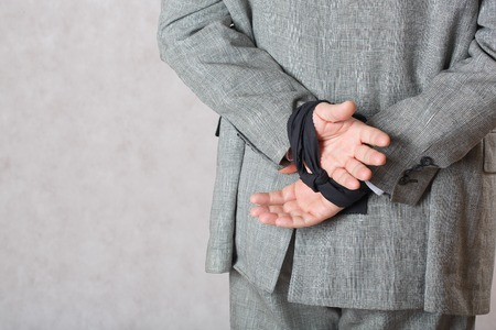 男は、背中の後ろに手を縛っていた。