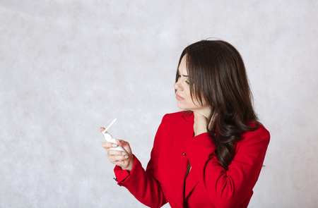 between 30 and 40 years: A young woman between 30 and 40 years old dressed in a formal manner has sore throat