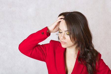 between 30 and 40 years: A young woman between 30 and 40 years old dressed in a classical red jacket shows a solution Stock Photo