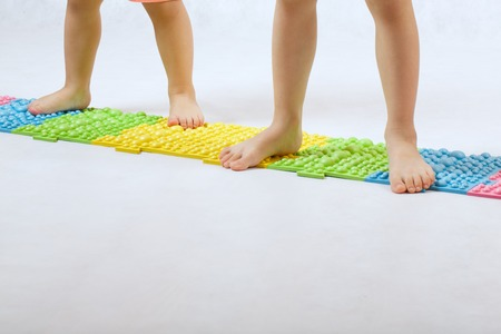 orthopaedic: The feet of small children on a orthopaedic mat. White background. Free space for a text. Stock Photo
