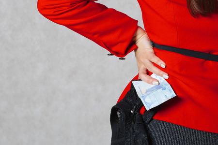 Una banconota in euro e una lingerie guipure nera in mano di una giovane donna.