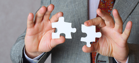 50 60 years: Pieces of puzzle in the hands of a business man. Closeup. Free space for a text