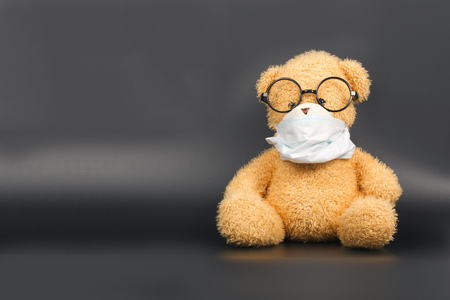 Teddy bear in a protective mask and eye glasses on a black background