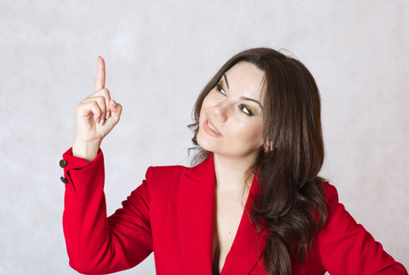 between 30 and 40 years: A young woman between 30 and 40 years old dressed in a classical red jacket show a solution