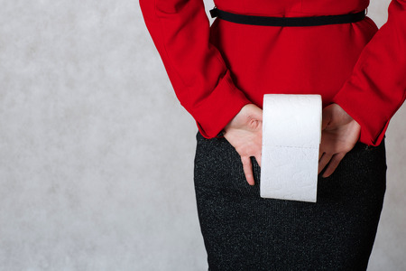 colorectal cancer: A young woman keeps a roll of a toilet paper close to her buttocks
