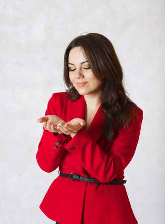 40 something: A young woman between 30 and 40 years old dressed in a classical red jacket opened her palms as if she had something on them.