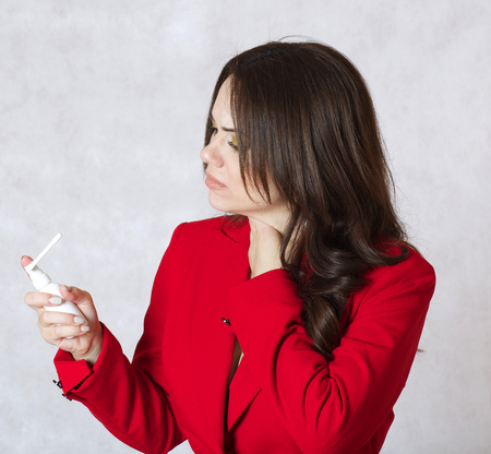 sore throat: A young woman between 30 and 40 years old dressed in a formal manner has sore throat