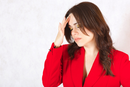 30 years old woman: A young woman between 30 and 40 years old dressed in a classical red jacket with a headache and stomachache. Stock Photo