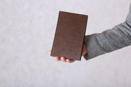 50 to 60 years: A man dressed in a classical costume keeps a brown book. Closeup