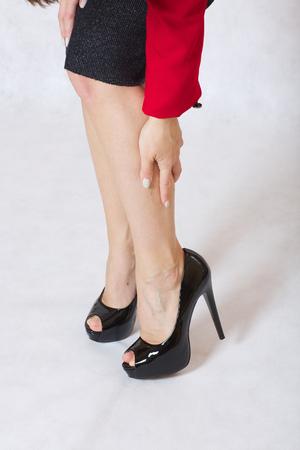 Młoda kobieta ma uczucie ciężkości w jej pięknych szczupłych nogach. Zdjęcie Seryjne