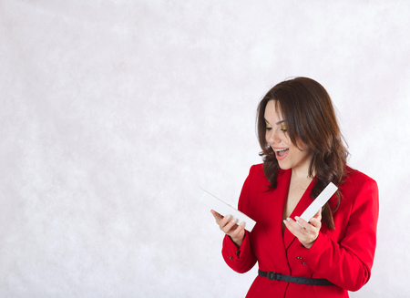 between 30 and 40 years: A young pretty woman between 30 and 40 years old,dressed in a classical costume opens a present box with a surprise. Stock Photo