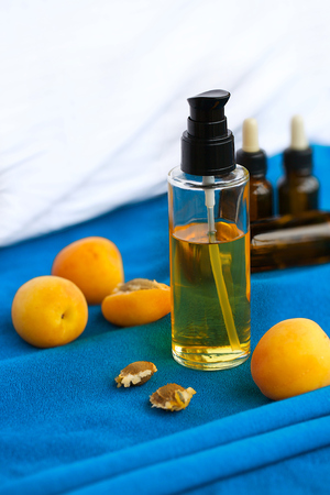 apricot kernel: Dispenser of apricot kernel oil on cyan fabric. Fresh apricots and kernel in the background.