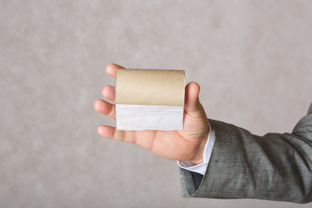 age 60: A man in a classical costume keeps a finished toilet paper roll. Closeup. Free space for a text.