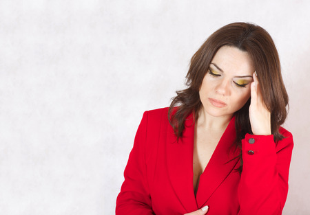 premenstrual syndrome: A young woman between 30 and 40 years old dressed in a classical red jacket with a headache and stomachache. Stock Photo