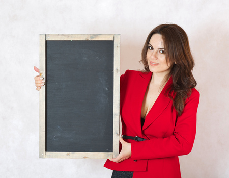 between 30 and 40 years: A young woman between 30 and 40 years old dressed in a formal way keeps a black chalk board. Free space for a text Stock Photo