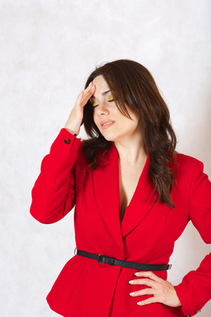 between 30 and 40 years: A young woman between 30 and 40 years old dressed in a classical red jacket with a headache and stomachache. Stock Photo