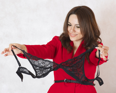 guipure: A young lady between 30 and 40 years old  observes a black guipure bra.