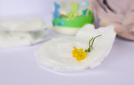 nursing bottle: A yellow flower on a nursing pad. Closeup. Milk,cheese cloth and breastfeeding bra in the background. Stock Photo