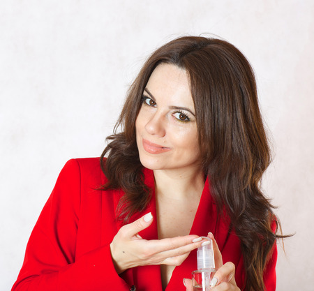 30 years old woman: A young woman between 30 and 40 years old dressed in a classical red jacket shows a glass bottle with hair oil.
