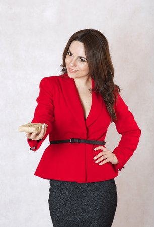 between 30 and 40 years: A young woman between 30 and 40 years old dressed in a classical red jacket gives a small parcel to someone,