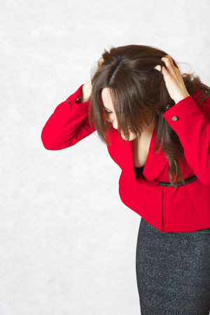 between 30 and 40 years: A young woman between 30 and 40 years old dressed in a classical red jacket itches her head skin Stock Photo